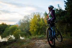 Изображение девушки с велосипедом в шлеме в осени Стоковые Изображения RF