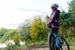 Изображение девушки с велосипедом в шлеме в осени Стоковое Изображение