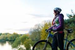 Изображение девушки с велосипедом в шлеме в осени Стоковое Изображение RF
