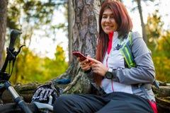 Изображение девушки с мобильным телефоном в лесе осени Стоковое Изображение RF