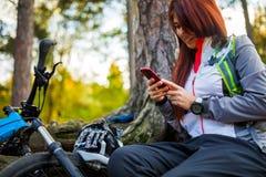 Изображение девушки с мобильным телефоном в лесе осени Стоковая Фотография RF