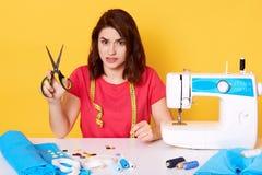 Изображение девушки atelier и различных инструментов в шить мастерской, женщине держит ножницы окруженный путем швейная машина, и стоковое изображение rf