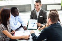 Изображение деловых партнеров обсуждая документы и идеи на встрече стоковое фото
