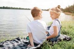 Изображение детей сидя совместно на одеяле и смотря один другого усмехаться девушки Она держит рыб-штангу в ей Стоковые Изображения RF