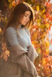 Изображение длинного с волосами брюнета смотря в сторону против предпосылки деревьев осени стоковые фото