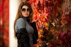 Изображение длинн-с волосами брюнета в солнечных очках на предпосылке плюща осени красного стоковая фотография