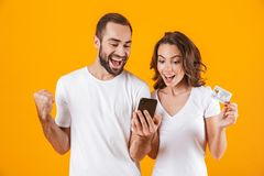 Изображение добросердечных человека и женщины пар используя сотовый телефон и кредитную карточку, изолированное над желтой предпо стоковое изображение