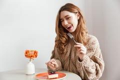 Изображение довольной кавказской женщины сидя на таблице и есть cak Стоковые Изображения