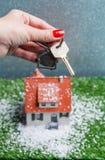 Изображение дома игрушки с падая снегом и рук с ключом Стоковая Фотография