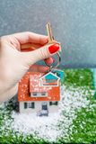 Изображение дома игрушки с падая снегом и рук с ключом Стоковые Фото