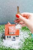 Изображение дома игрушки с падая снегом и рук с ключом Стоковое Фото
