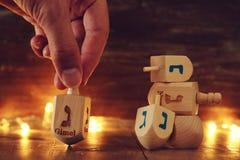 Изображение еврейского праздника Хануки с деревянным собранием dreidels & x28; закручивая top& x29; и света гирлянды золота стоковое фото