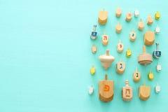 Изображение еврейского праздника Хануки с деревянным собранием dreidels & x28; закручивая top& x29; над предпосылкой мяты стоковая фотография