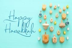 Изображение еврейского праздника Хануки с деревянным собранием dreidels & x28; закручивая top& x29; над предпосылкой мяты стоковое фото rf
