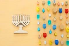 Изображение еврейского праздника Хануки с деревянным собранием dreidels & x28; закручивая top& x29; над пастельной желтой предпос стоковое фото
