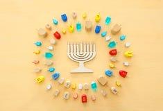 Изображение еврейского праздника Хануки с деревянным собранием dreidels & x28; закручивая top& x29; над пастельной желтой предпос стоковая фотография
