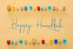 Изображение еврейского праздника Хануки с деревянным собранием dreidels & x28; закручивая top& x29; над пастельной желтой предпос стоковые фотографии rf