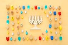 Изображение еврейского праздника Хануки с деревянным собранием dreidels & x28; закручивая top& x29; над пастельной желтой предпос стоковые изображения