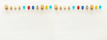 Изображение еврейского праздника Хануки с деревянным собранием dreidels & x28; закручивая top& x29; над белой предпосылкой стоковое изображение