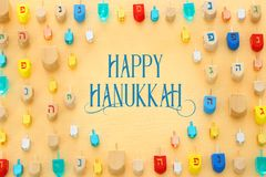 Изображение еврейского праздника Хануки с деревянным собранием dreidels & x28; закручивая top& x29; над пастельной желтой предпос стоковое изображение