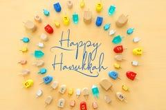 Изображение еврейского праздника Хануки с деревянным собранием dreidels & x28; закручивая top& x29; над пастельной желтой предпос стоковое фото rf
