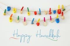 Изображение еврейского праздника Хануки с деревянным собранием dreidels & x28; закручивая top& x29; над белой предпосылкой стоковая фотография