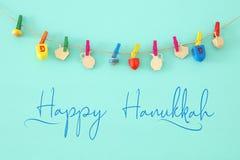 Изображение еврейского праздника Хануки с деревянным собранием dreidels & x28; закручивая top& x29; над предпосылкой мяты стоковые фото