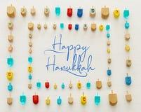 Изображение еврейского праздника Хануки с деревянным собранием dreidels & x28; закручивая top& x29; над белой предпосылкой стоковые фотографии rf