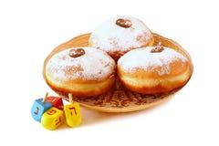 Изображение еврейского праздника Хануки с donuts и деревянными dreidels (закручивая верхняя часть) Изолировано на белизне Стоковые Изображения RF