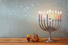 Изображение еврейского праздника Хануки с menorah (традиционными канделябрами) и деревянными dreidels (закручивая верхняя часть)