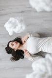 Изображение девушки лежа на поле в облаках Стоковые Изображения