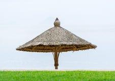 Изображение деревянного зонтика на пляже на временени Стоковые Фото