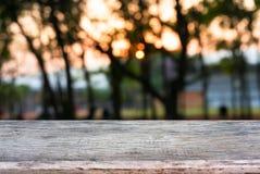 Изображение деревянного стола перед предпосылкой запачканной конспектом стоковое изображение rf