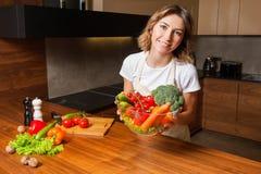 Изображение женщины в кухне держа салат плиты стоковые изображения