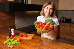Изображение женщины в кухне держа салат плиты стоковые изображения rf