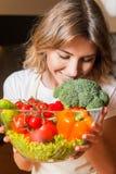 Изображение женщины в кухне держа салат плиты стоковая фотография rf
