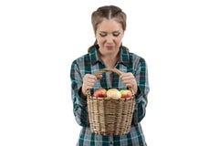 Изображение женщины смотря корзину с яблоками Стоковые Фотографии RF