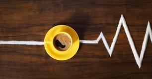 Изображение желтых кофейной чашки и поддонника на таблице Стоковые Фото
