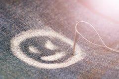 Изображение жизнерадостной стороны, улыбка, нарисованная с мелом на джинсах Игла и резьба стоковое фото