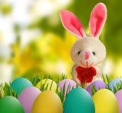 Изображение зайца игрушки и пасхальных яя в крупном плане травы Стоковые Изображения