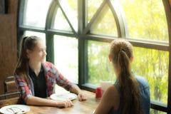 Изображение запачкало для молодой женщины предпосылки 2 сидя на таблице ждать ее еду Усмехаясь девушка смотря из окна Стоковое Фото