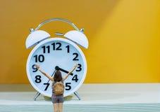 Изображение за женщиной поднимает их будильник предпосылки рюкзака оружий и плеча с белой и черной шкалой на апельсине стоковое фото rf