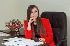 Изображение задумчивой коммерсантки с документами и кофе в красном костюме сидя на таблице с документами Стоковые Фото