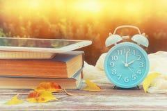 Изображение изменения времени осени Понижается назад концепция Высушите листья и винтажный будильник на деревянном столе outdoors стоковые фото