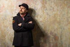 Изображение кавказского человека с grungy светлыми волосами одело тепло в стильном черном пальто канавы и в стиле фанк шляпе и ша стоковая фотография rf