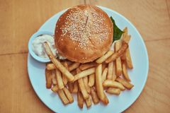 Изображение конца-вверх гамбургера с фраями француза и пряным соусом на белой плите Нездоровая принципиальная схема еды Стоковое Изображение