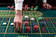 Изображение конца-вверх живое зеленой таблицы казино с рулеткой, с руками крупье и пестротканых обломоков Стоковое фото RF