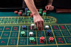 Изображение конца-вверх живое зеленой таблицы казино с рулеткой, с руками крупье и пестротканых обломоков Стоковые Изображения RF