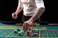 Изображение конца-вверх живое зеленой таблицы казино с рулеткой, с руками крупье и пестротканых обломоков Стоковое Изображение RF