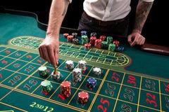 Изображение конца-вверх живое зеленой таблицы казино с рулеткой, с руками крупье и пестротканых обломоков Стоковые Изображения